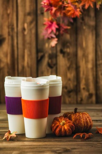 Reusable coffee cups with pumpkins and leaves. Fall arrangement