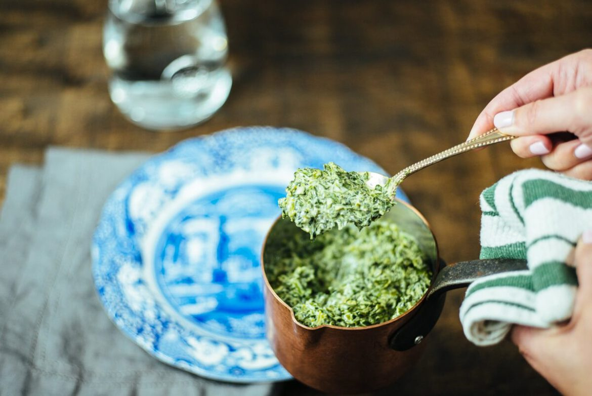 serving steakhouse style creamed spinach recipe by The Taste Edit from a copper pot for a date night
