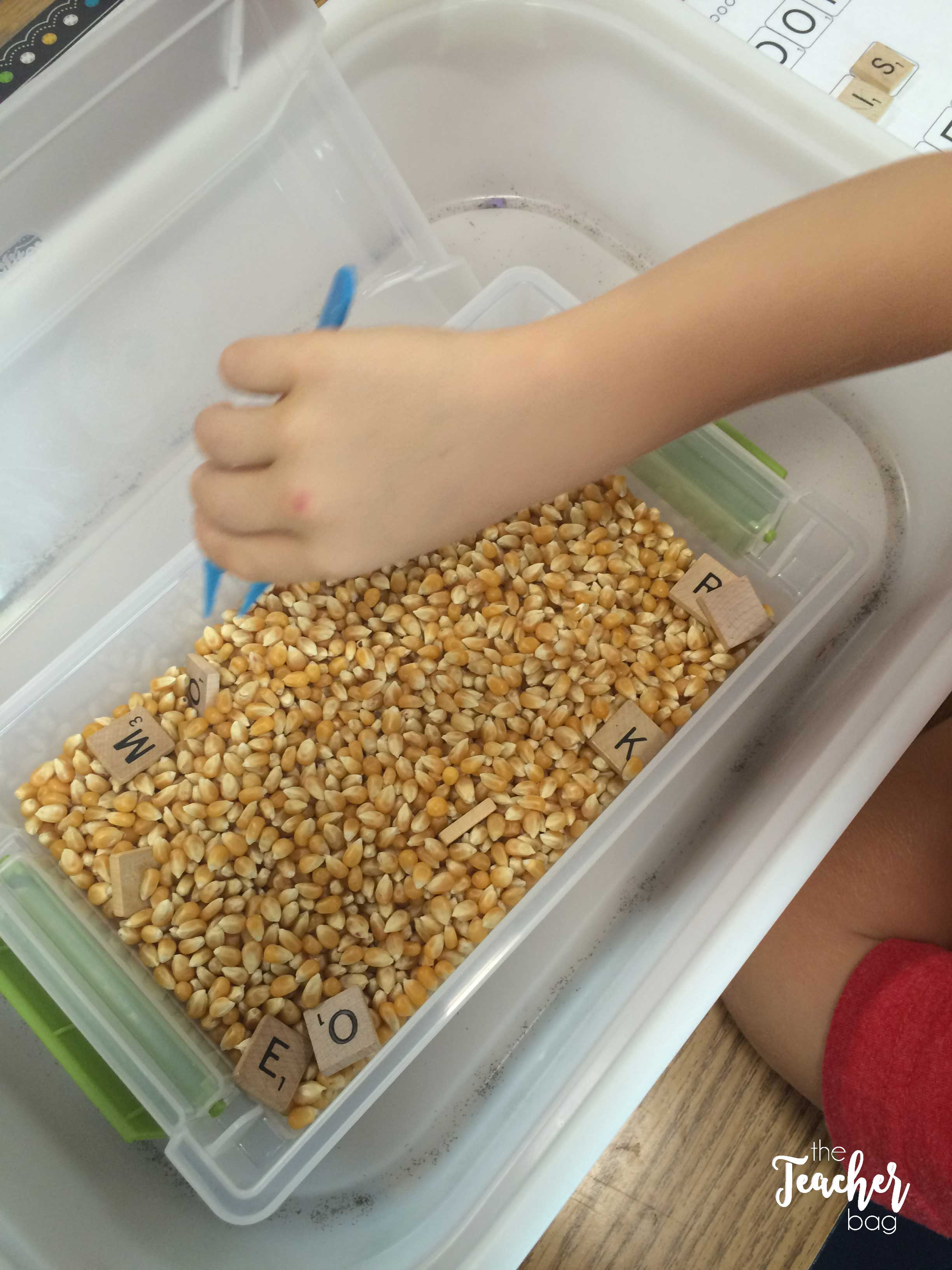 Use tweezers to search for scrabble tiles in popcorn. This helps to build fine motor skills.