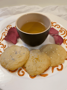 A cup of The Tea In Me Sakura Novella tea surrounded by sugar cookies and rose petals