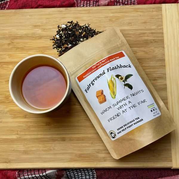 A cup of The Tea In Me Fairground Flashback tea with the bag and loose tea leaves.