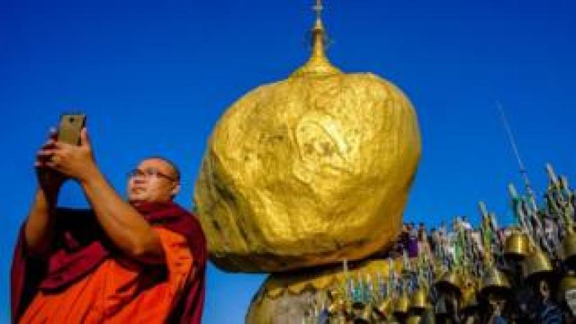 Buddhist monk takes a selfie in front of a gold rock