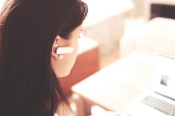 woman wearing a bluetooth ear piece