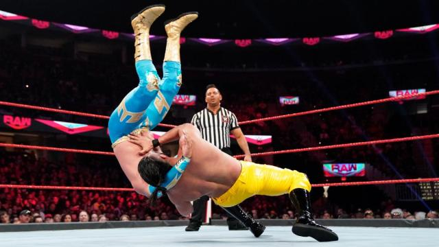 Andrade throwing Sin Cara down with the Three Amigos via WWE.com