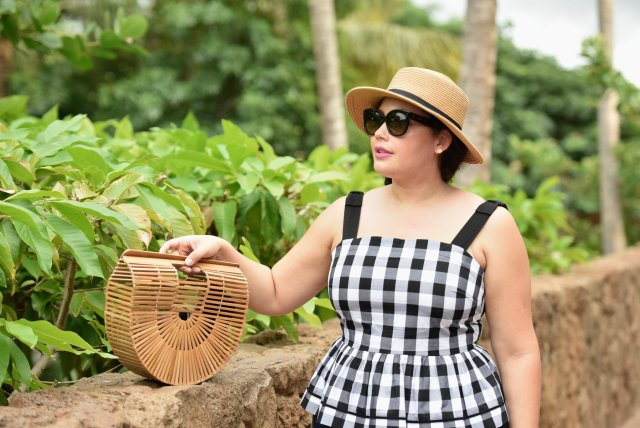 Image shows Tanesha in a black and white gingham sundress, in a straw hat, sunglasses and a straw bag in Hawaii