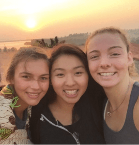 Image description: From left to right, Sydney Baumgardt, Grace Wong (author) and Nell Shea watching the sunrise over lake at Gashora Girls Academy, Rwanda
