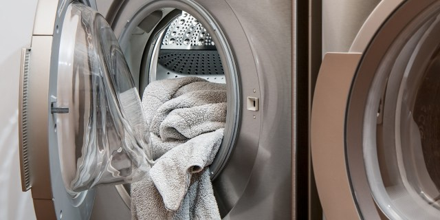 Gray towels hang out the front of a laundry machine.