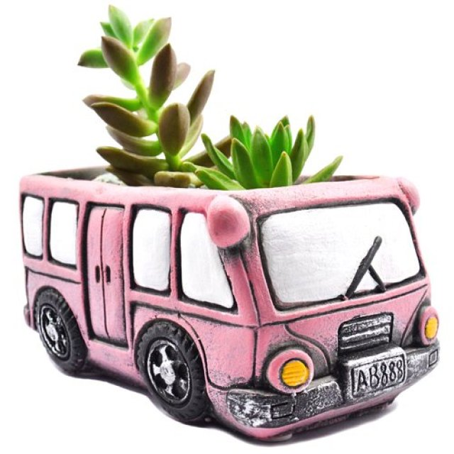 Image description: A retro pink bus with black details and white windows holds green succulents.