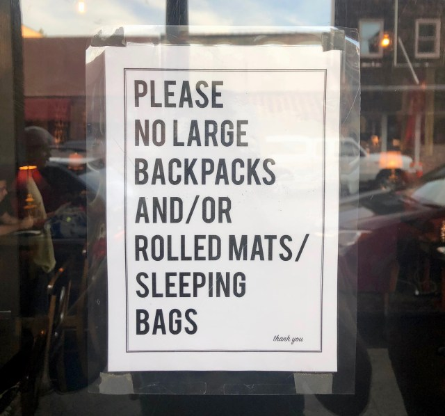 """White sign with black letters posted on glass saying """"Please no large backpacks and/or rolled mats/sleeping bags. thank you."""""""