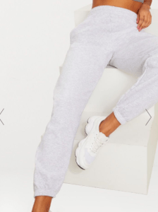 Image via Pretty Little Thing [Image description: a woman modeling grey sweatpants, leaning on white stairs]