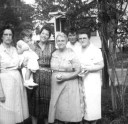 """Gulfport, Harrison, Mississippi, USA  Bama Smith Grayson, Tenderly Rose Bosworth held by Janie Morris Bosworth, Rosie S. Morris, Patsy Grayson Gendron and Helen Hoagland Bosworth Mason standing together on front yard of """"Hungry Hill"""" at 1711 Wisteria Street."""