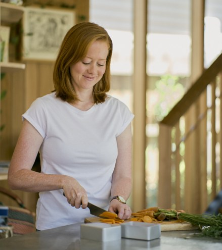 Erin Rhodes. A woman wih red hair wearing a white tshirt cuts vegetables in the kitchen.
