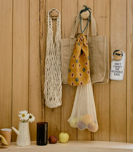 Reusable bags hanging on a wall near a door at home. There is a sign saying don't forget the resuable bags.