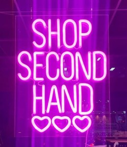 A pink fluroescent sign says SHOP SECOND HAND with three love hearts underneath
