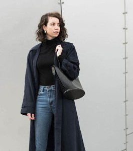 A woman wears a long dark jacket, blue jeans, a black turtle neck and has a black bag over her shoulder.