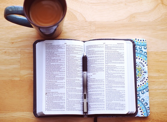 A bible on a table with a cup of coffee, a journal, and a pen