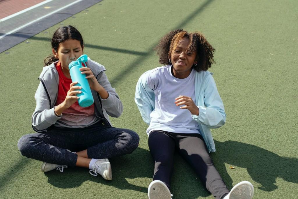 multiethnic girls resting on stadium after training