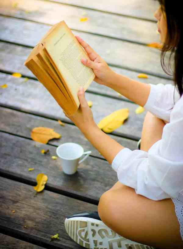 young woman sitting on the park and reading the book