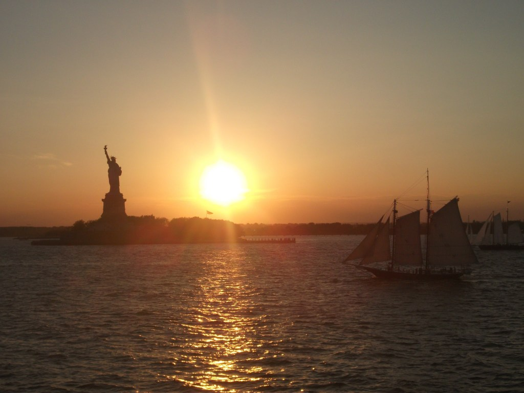 The sun setting behind the Statue of Liberty complete with little sail boat.
