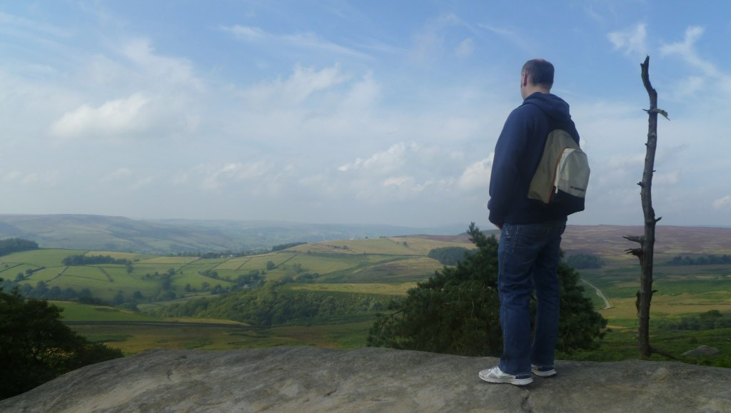 Andrew looking over the surrounding Farmland from Stanage Edge in the Peak District