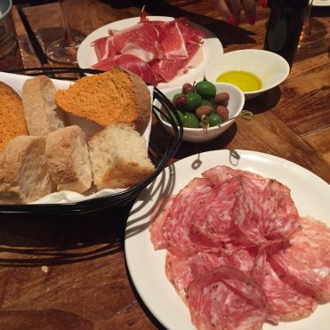 Antipasti selection of hams, olives and bread