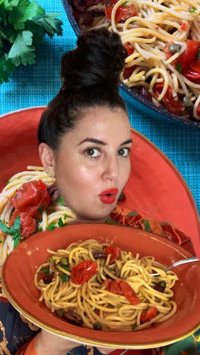 Paola, the Tiny Italian, holding a coral orange ceramic bowl of spaghetti alla puttanesca with fresh cherry tomatoes, black olives and capers. She is standing in front of a blue background with more dishes of spaghetti Alla puttanesca