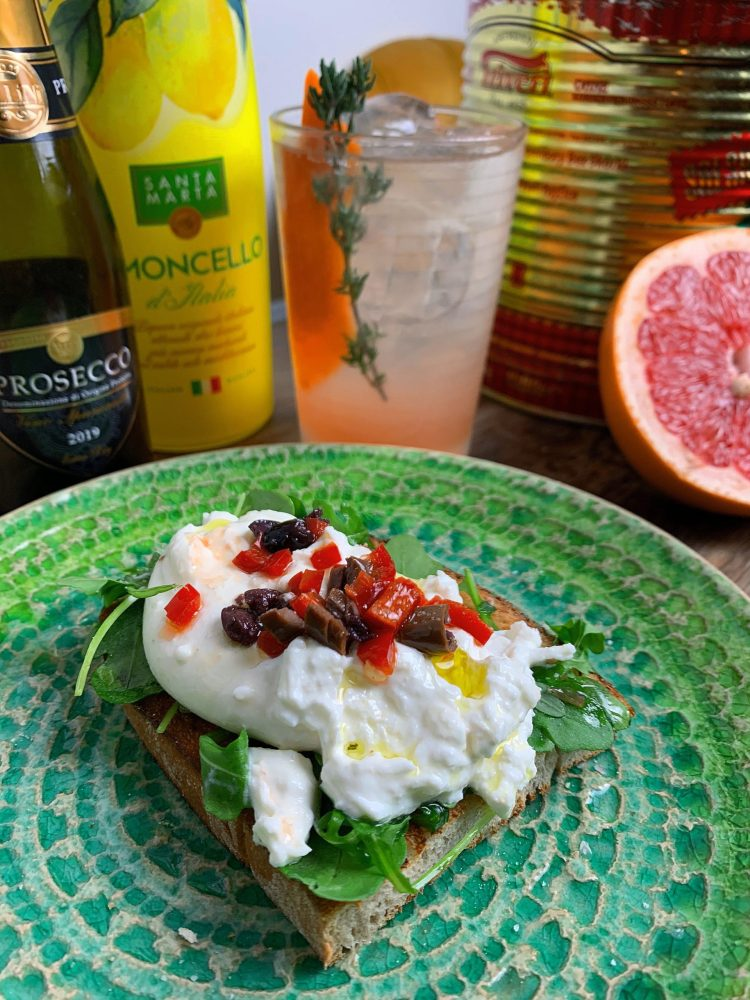 Burrata sat on toasted bread and rocket leaves. Topped with chopped red chill and black olives