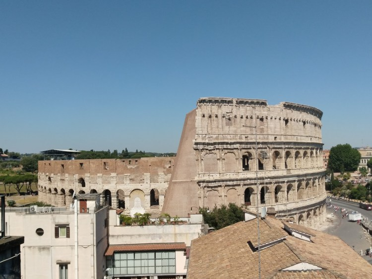 Clear blue sky and the colosseum from a rooftop two buildings away.