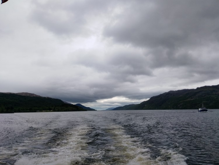 View of Loch Ness from the tour boat on a cloudy day. The wake of the boat stretches back far, and the two hills on either side spill into the lake and almost converge in the distance.