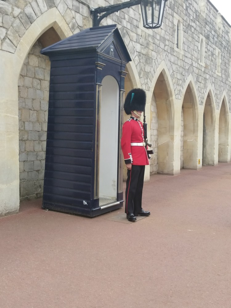 A Windsor Guard in his red suit and funny hat in front of his post.