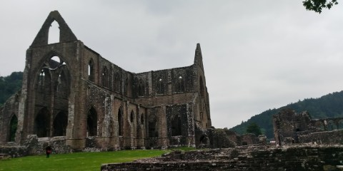 The outside of Tintern Abbey with a cloudy sky