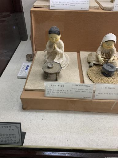 Small statues of the same Korean woman performing various tasks in the wine making process. Small placards explain each step jeonju travel guide