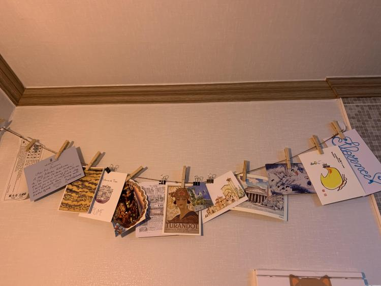 A selection of postcards attached to a length of twine by clothespins suspended on a wall.