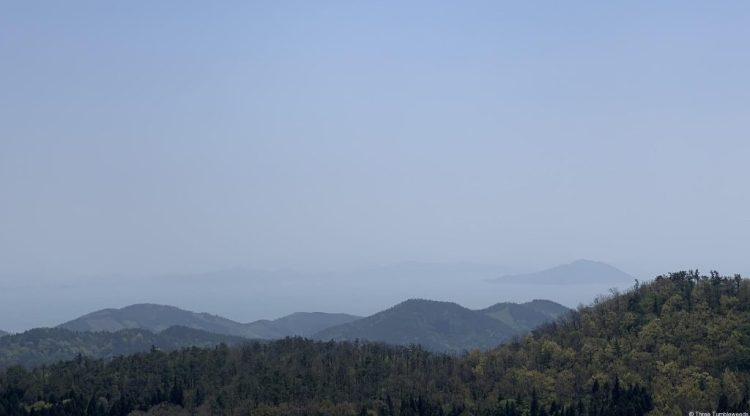 Layers of mountains fading into the ocean in Boseong travel guide. The islands in the distance are just visible, looking like they almost hover in the air from how pale the sea is.