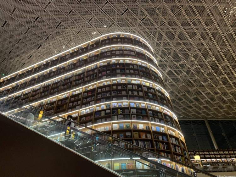 rows and rows of bookshelves going up to a towering ceiling, an escalator giving an idea of the scale. The bookshelves are curved and outlined with white lights,