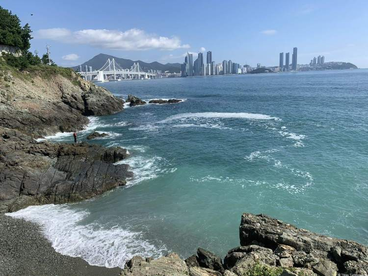 Igidae in Busan travel guide a rocky shore in the foreground and left with azure waters lapping at rocky sand. As the water becomes deeper the blue darkens and leads up to the city and mountains on the other side of the bay.