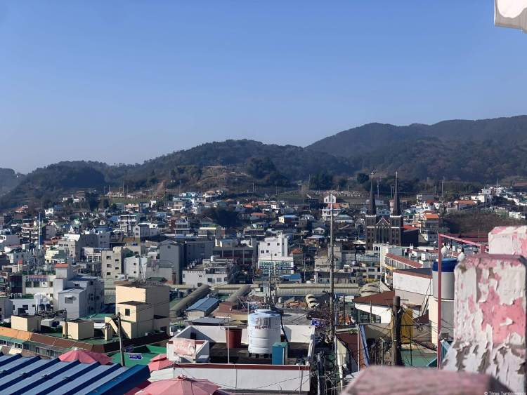 view of the city from above, mountains in the background. The buildings are in shades of pastel in the foreground and more muted colors in the midground