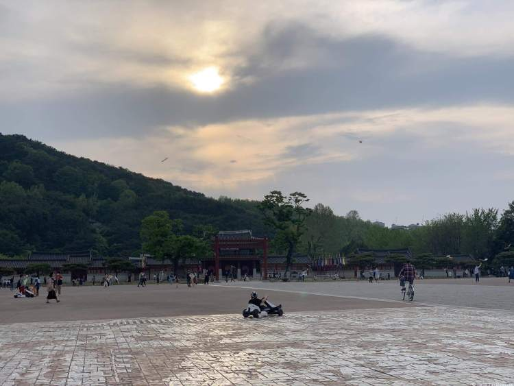 sunset view of the huge square. Mountains are in the background along with the facade of the Temporary Palace. Children fly kites and play.