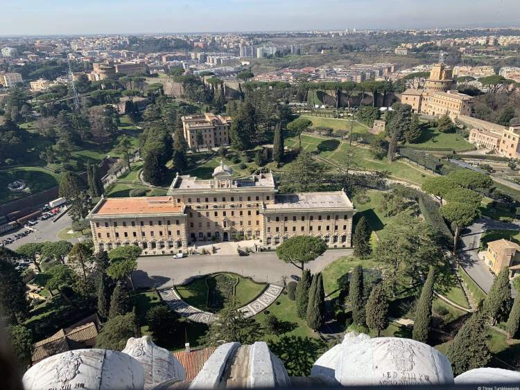 A view of Vatican City and Rome from far above. Many pine trees and umbrella trees, and a large three wing building with a circular courtyard area is in the middle.