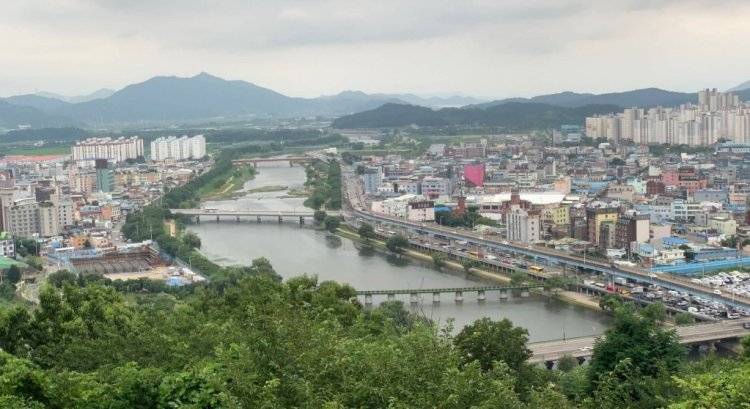 a view on Suncheon travel guide from above, the city is split by a river. A bottom border of treetrops. The river is wide with three bridges across it.