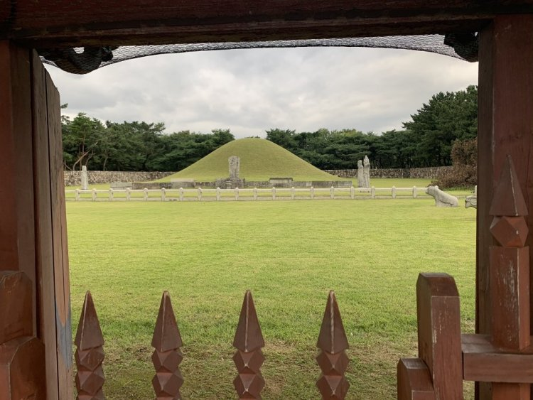 View through a brown picket gate of King Suro's green tomb mound.
