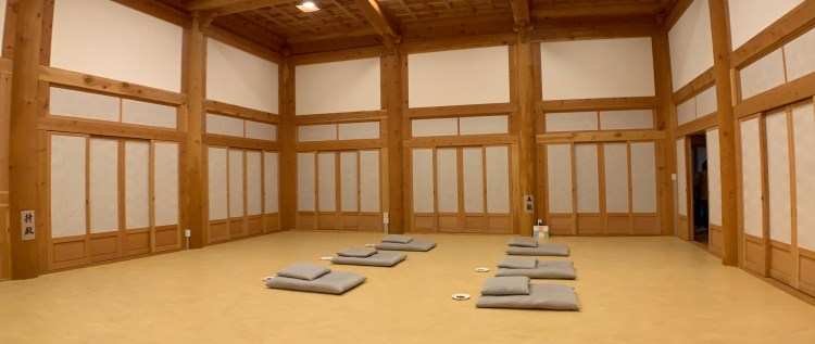 A wood decorated room with six small mats with small pillows on top of each other set across from each other on the floor.