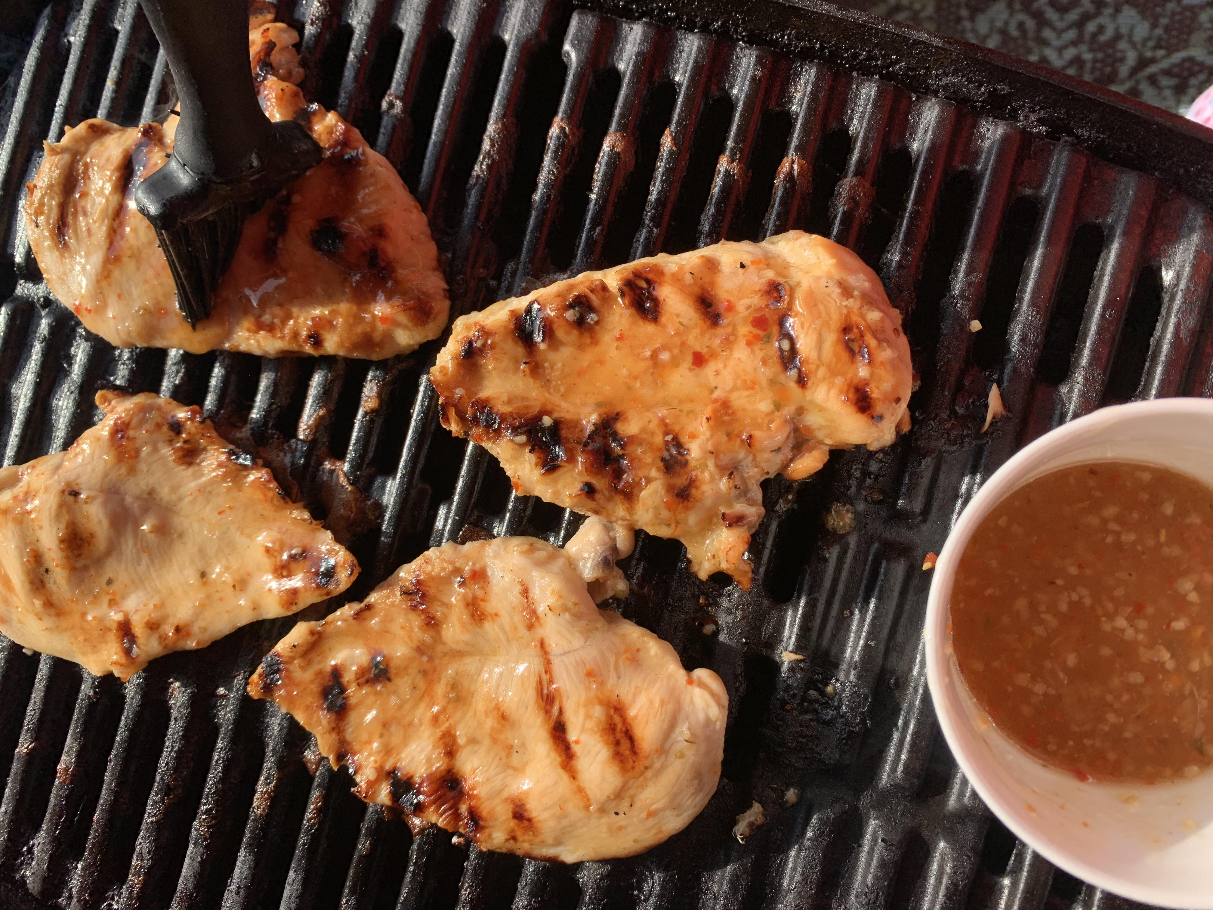 4 Chicken breasts on a weber grill being basted with Italian dressing.