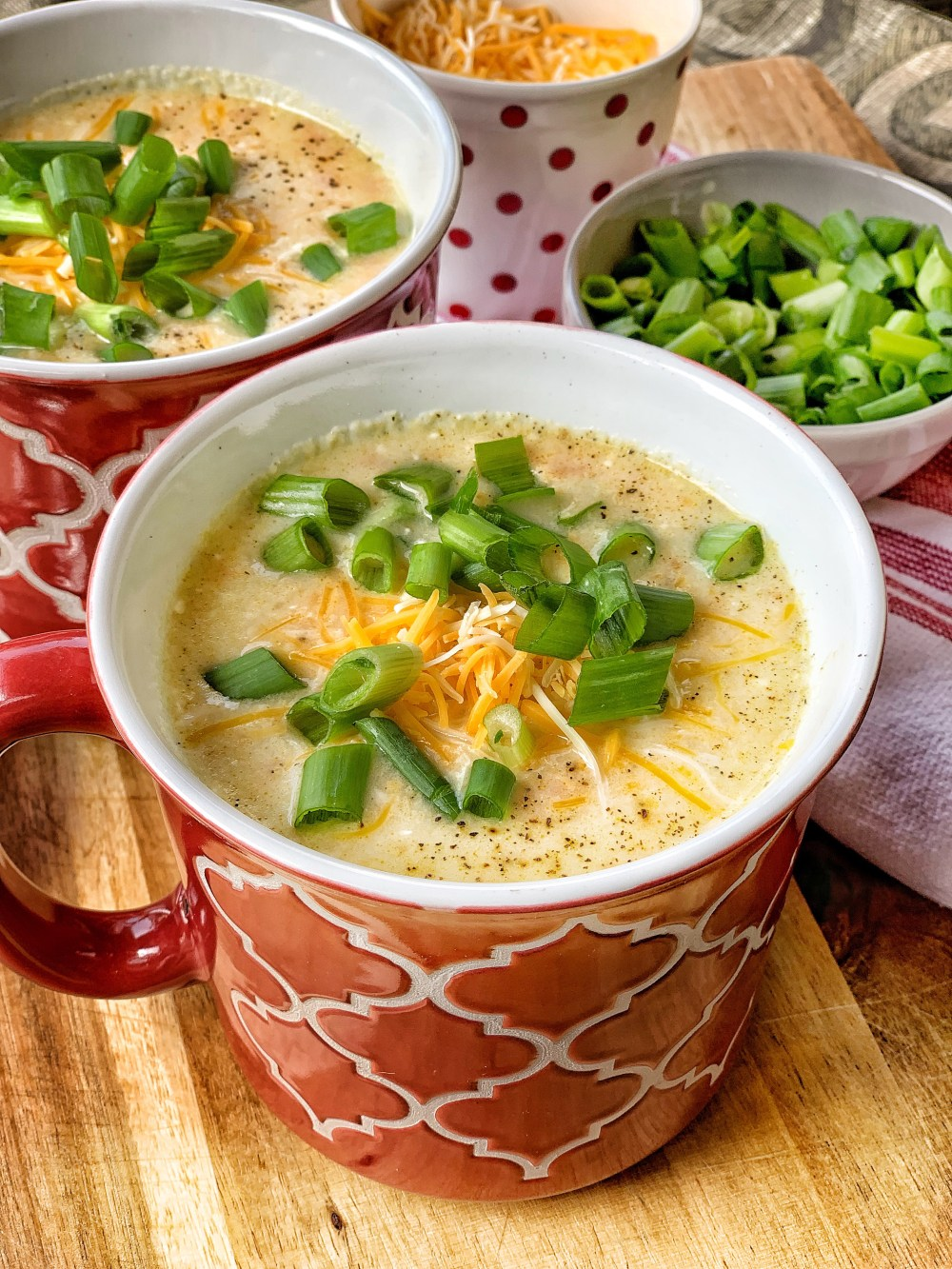 Two mugs of potato soup with cheddar cheese and green onions.