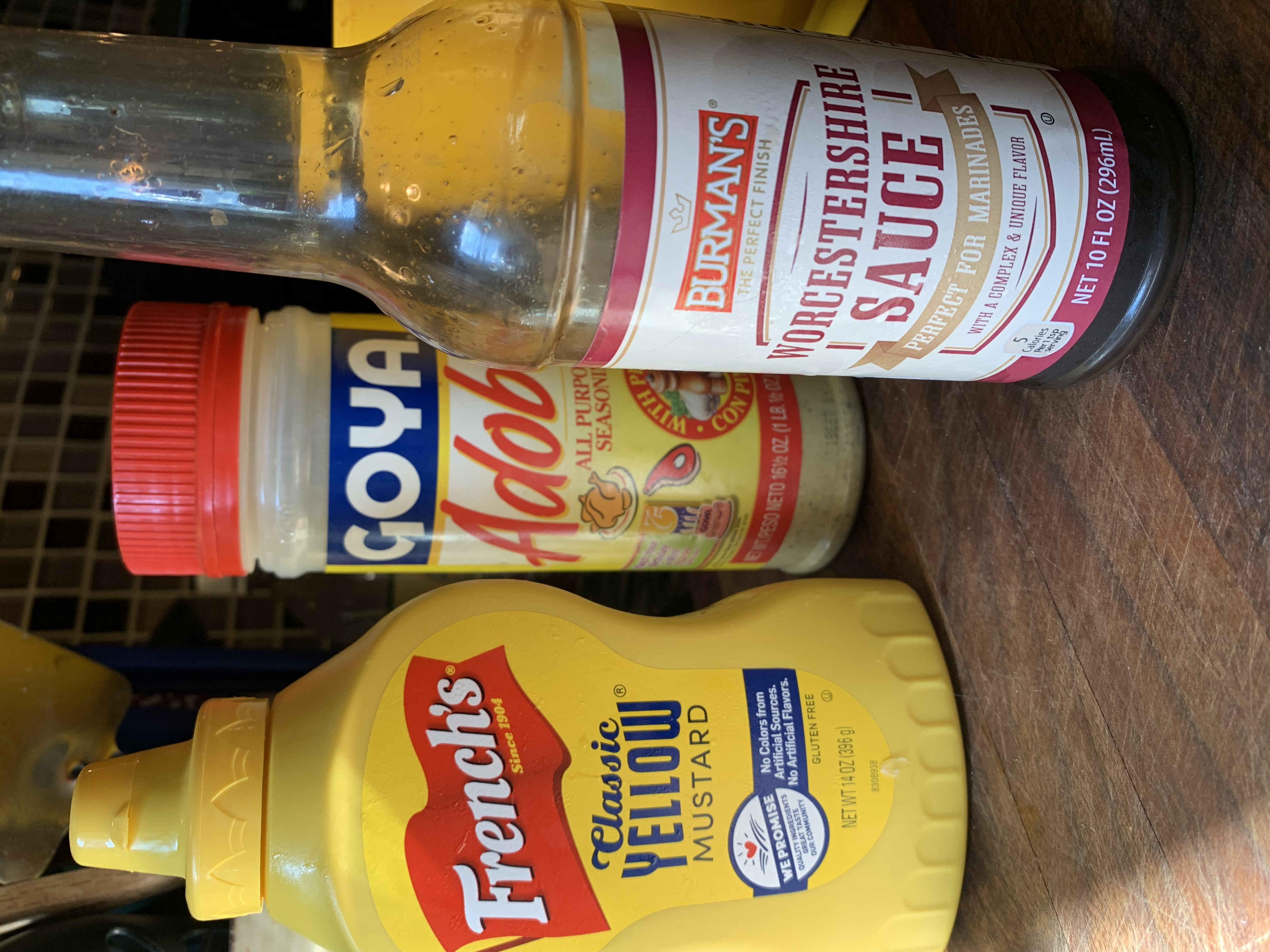 Three bottles containing mustard, Worcestershire sauce and seasoning salt.