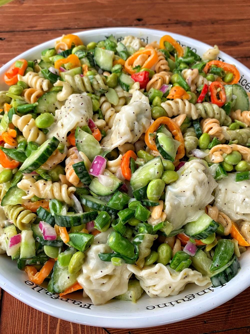 A bowl of veggies and corkscrew pasta.
