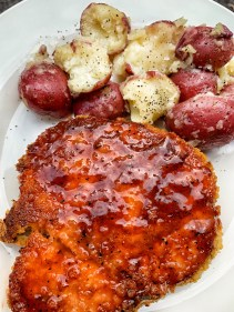 Pork chop with bbq sauce on top and red potatoes with butter