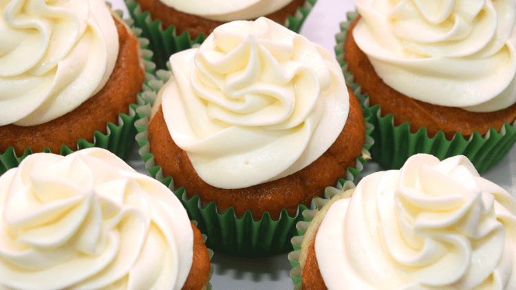 A close up view of multiple pumpkin cheesecake cupcakes all frosted with cream cheese buttercream frosting.