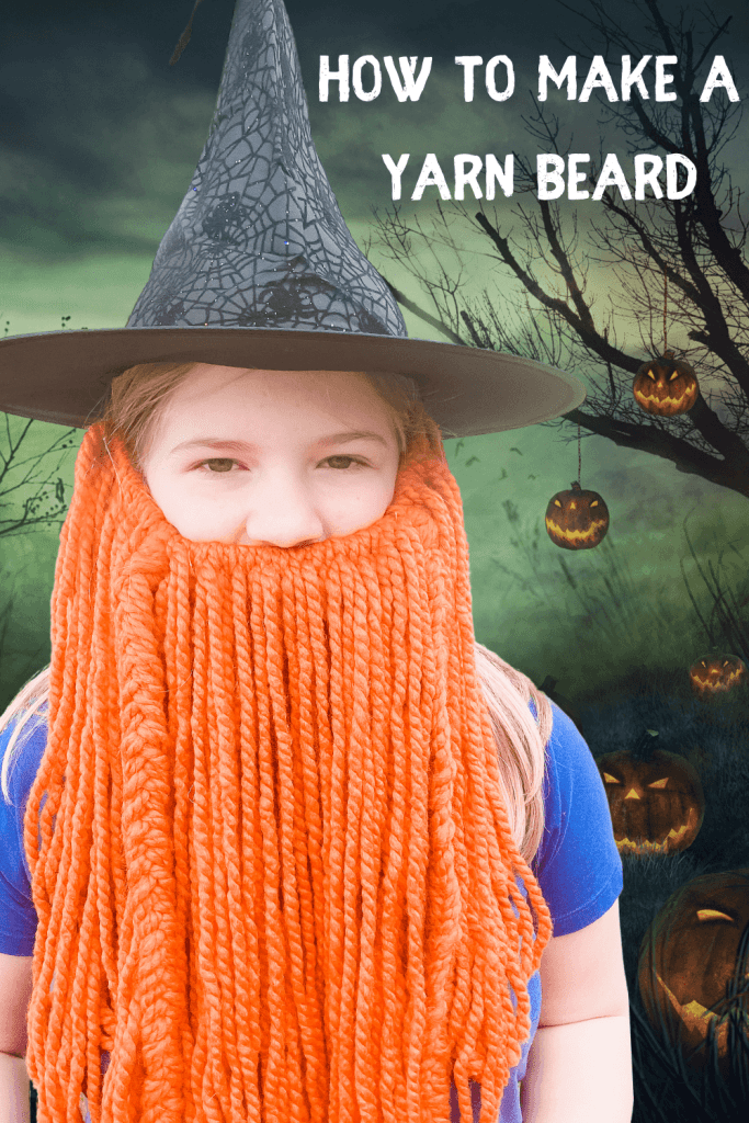 A little girl in a witch hat and a yarn beard.