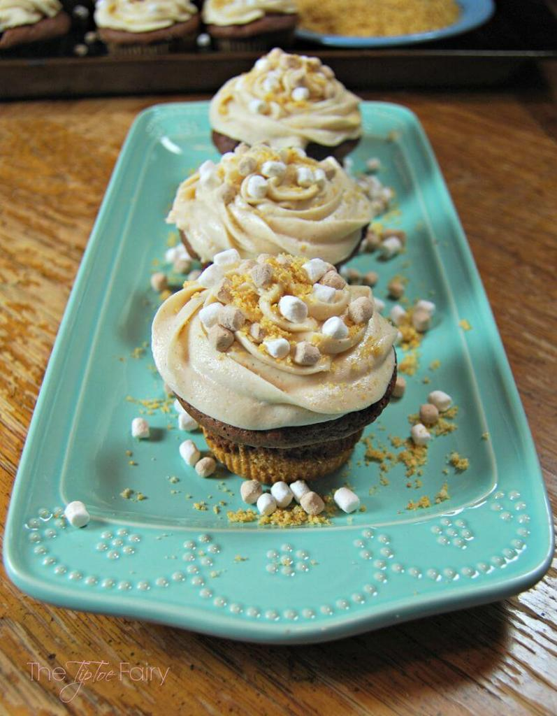 Rectangular aqua plate on a wooden table with 3 S'mores Cupcakes in a row.